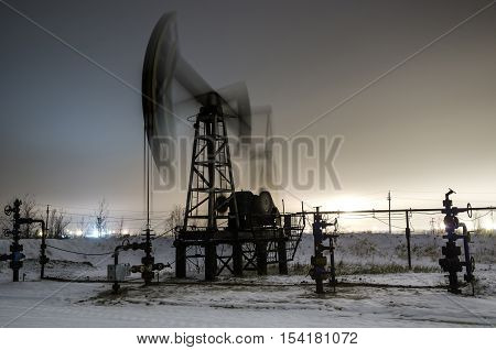 Working oil pump at night time. Oilfield during winter. Refinery lights background. Oil and gas concept. Motion blur.