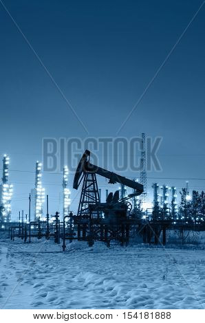 Oil pump and wellhead at the background of refinery by night. Oilfield during winter. Oil and gas industry. Blue toned.