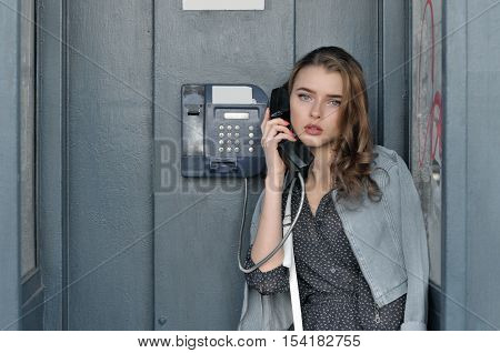 Girl Holding A Payphone Handset In Her Hand