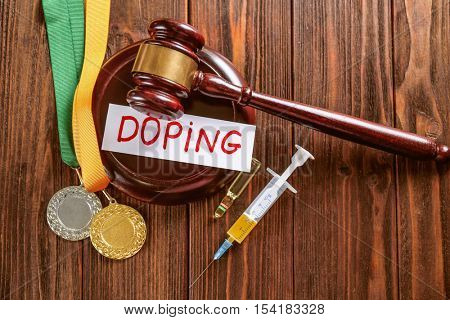 Gavel, word Doping and syringe on wooden background