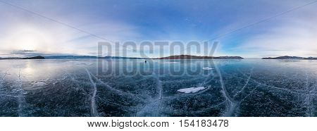 Blue Ice Of Lake Baikal Covered With Cracks, Cloudy Weather At Sunset.