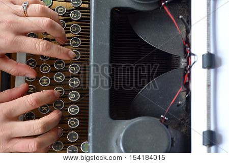 Hand of a young woman writer writing on antique typewriter. Above view - Type Writing Concept