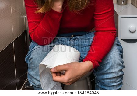 Woman Holding Toilet Paper Roll In Restroom - Diarrhea Concept