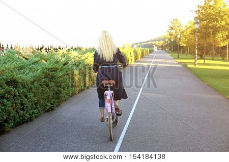 Young woman riding bicycle in park along bikeway