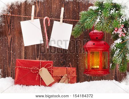 Christmas candle lantern and blank photo frames. Focus on gift boxes