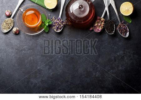 Tea cup and assortment of dry tea in spoons on stone table. Top view with copy space