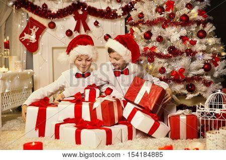 Christmas Children Opening Present Gift Box Kids Boys in Santa Hat Xmas Tree Interior