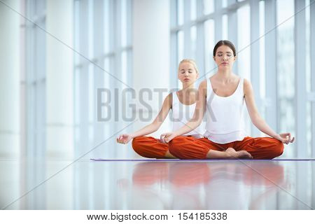 Young women practicing yoga indoors