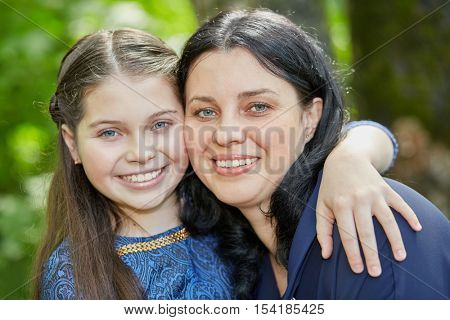 Closeup portrait of smiling teenage girl and dark-haired wooman embracing in summer park.