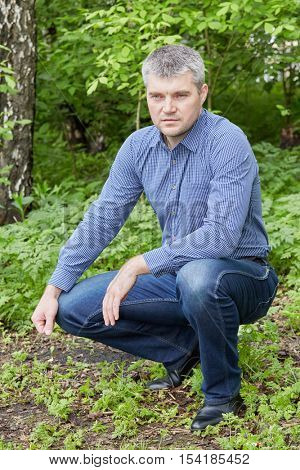 Portrait of grey-haired man in checkered shirt sits squatted at summer park.