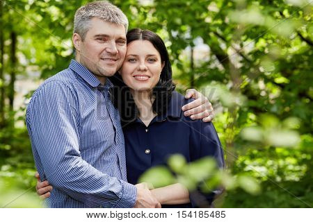 Half-length portrait of grey-haired man and dark-haired wooman standing embraced in summer park.
