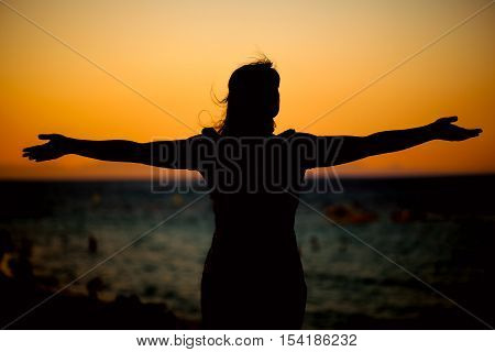Young woman relaxing in summer sunset near sea