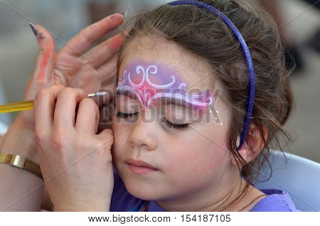 Little Girl Getting Her Face Painted By Face Painting Artist