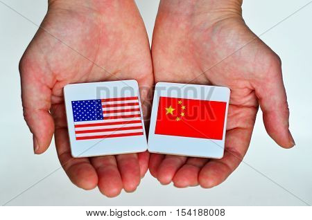 Two Hands Holds The National Flags Of The United States Of America (l) And Of The Republic People Of