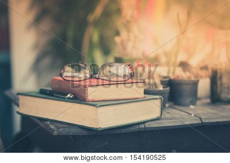 Glasses with books and pen on wood table in morning time. weekend lifestyle concept. focus on red vintage book spine with vintage filter effect