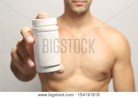Muscular man holding drugs in bottle, closeup