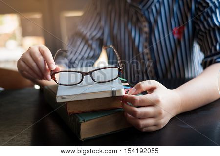 Morning lifestyle scene of young hipster woman put her glasses down on books stack in cafe. Weekend activity or hobby concept