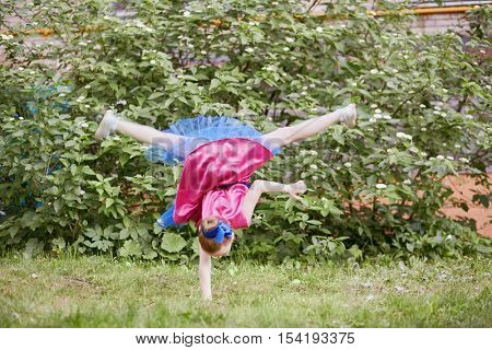 Little girl in dancing suit stands on one arm upside down at grassy lawn.
