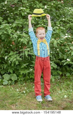 Little red-haired boy with open mouth dressed in dance suit holds yellow hat above his head outdoors.