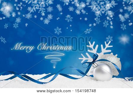 Blue ornament with white snow and snowflake on shiny blue background. Merry Christmas background with silver and shiny balls with blue ribbon and copy space. Xmas holiday and blue decoration on snow.