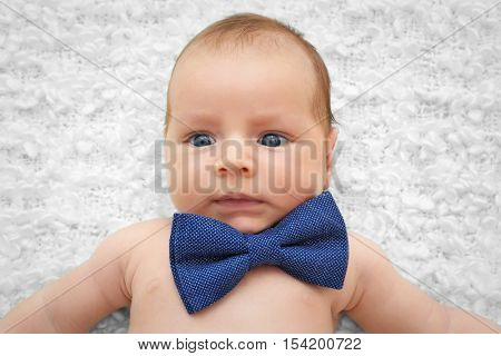 Cute baby with bow tie lying on white bedspread
