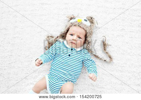 Cute baby with funny knitted cap lying on white bedspread, close up view