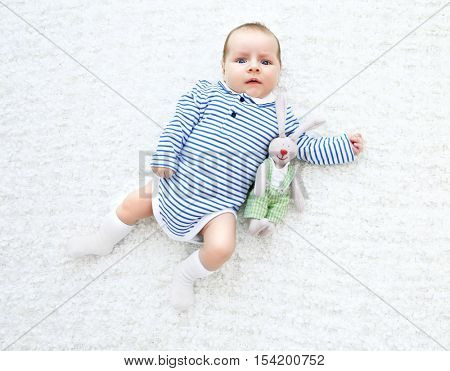 Cute baby with cuddly rabbit lying on white bedspread