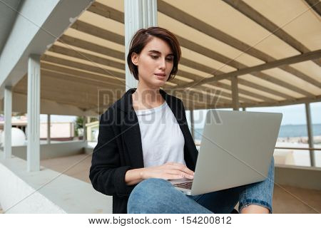 Serious beautiful young woman using laptop in verandah on the beach