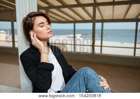 Relaxed young woman sitting with eyes closed and listening to music in gazebo on seashore