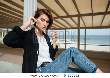 Attractive young woman sitting and listening to music with earphones in verandah on the seaside