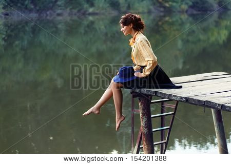 Side view of dreaming girl sitting on jetty forest and river on background. Beautiful woman sitting by the lake. Lonely woman sitting on a wooden bridge