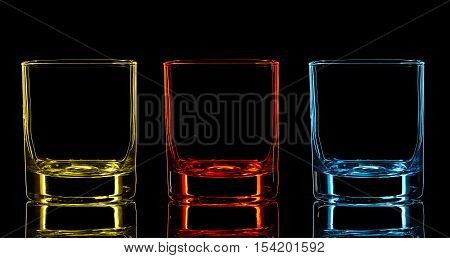 Silhouette of color strong liquor classic glass on black background