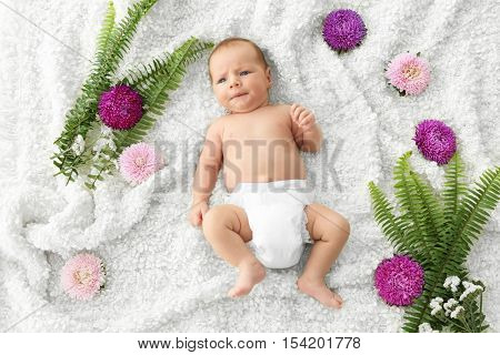 Cute baby lying on bedspread among flowers and fern leaves