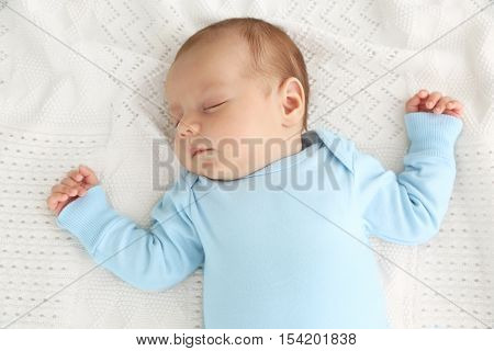 Portrait of cute baby sleeping on bedspread, close up view