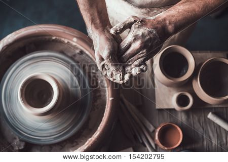 Potter at work. Top view of potter standing near pottery wheel and holding hands together