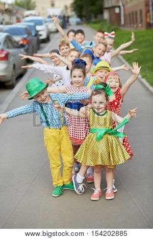 Fifteen children stand one by one outstretching arms to sides at sidewalk, focus on first girl.
