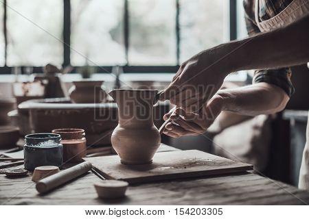 Making perfect jug. Close-up of potter making ceramic jug on at his workshop