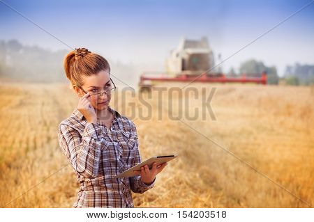 Pretty Farmer Girl In Glasses Keeps A Crop Accounting On The Tablet In Wheat Field