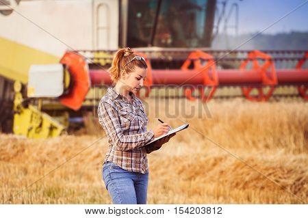 Pretty Farmer Girl In Glasses Keeps A Crop Accounting In The Folder In Wheat Field