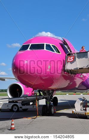 KATOWICE - JULY 2: Wizzair Airbus A320 is being prepared for the takeoff crew is preparing the plane for flight on July 2 2015 in Katowice Airport Poland. Wizzair is one of the largest low-cost airlines.