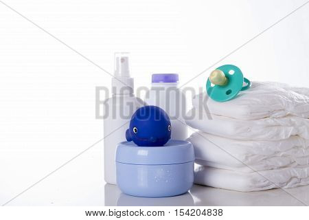New born child stack of diapers nipple rubber toy and baby cream on a white background