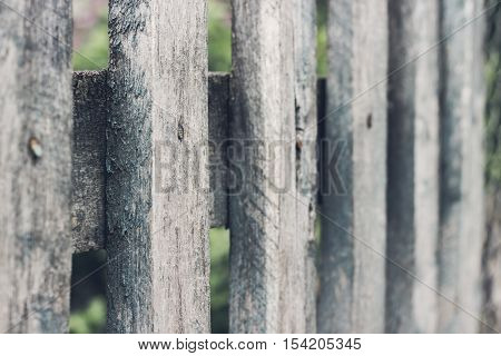 Close up of old grey wooden picket fence panels. Vintage wood background. Selective focus
