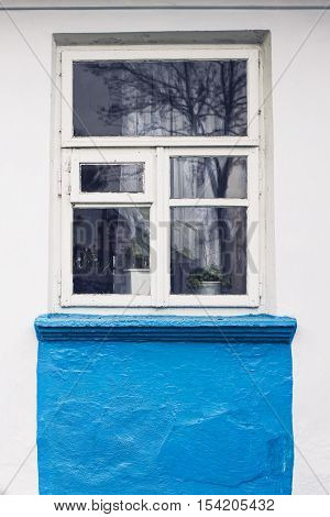 White wooden frame window in old Ukrainian village house with whitewash wall partly pained in blue