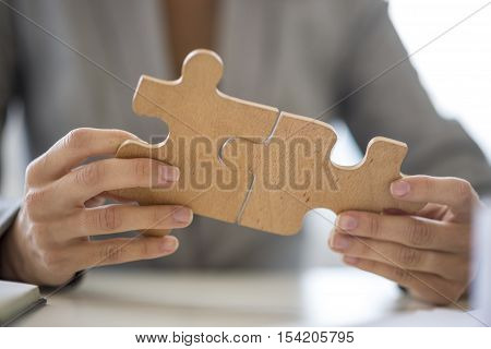 Close up on unidentifiable business person with hands putting together two puzzle pieces.