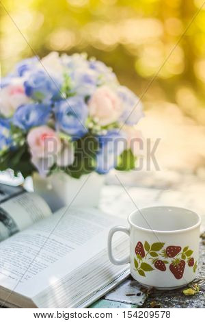 Cup of coffee with flower desksoft focus background blur book