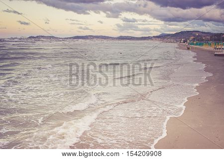 Beautiful landscape of the sand coast with dramatic sky and rolling waves. Stormy weather