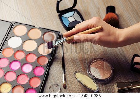 Female makeup artist hand with cosmetics at work