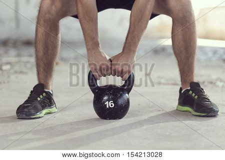Detail of a sportsman lifting a kettlebell weight as a part of a hard workout