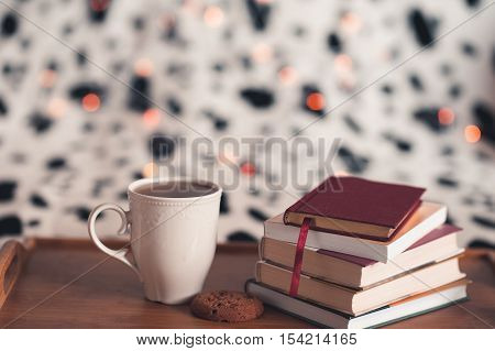 Cup of tea staying on wooden tray with stack of books an cookie over Christmas lights closeup. Cozy morning. Resting in bed.