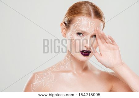Pretty model with body art looking at the camera. Close up. hand near face